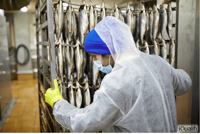 A man moves a rack of fish.  Mercury in fish is a naturally occurring process.